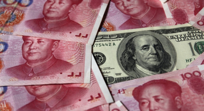 a-100-banknote-is-placed-next-to-100-yuan-banknotes-in-this-picture-illustration-taken-in-beijing-oct-16-2010