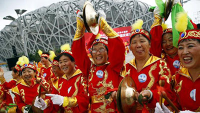 Performers cheer ahead of IOC's announcement of the winner city for the 2022 winter Olympics bid, outside the Birds' Nest, also known as the National Stadium, in Beijing