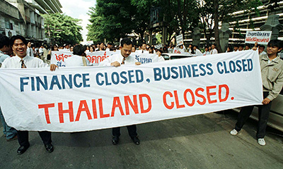 Employees of suspended finance companies carry a banner during a rally in Bangkok in November 1997